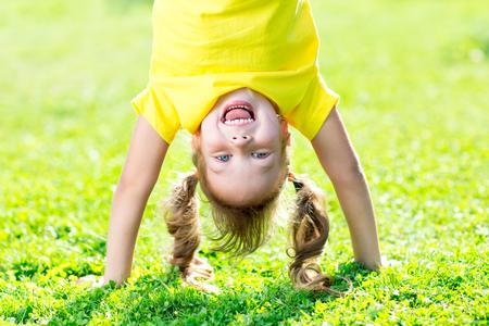 Retratos de Miúdo feliz que joga de cabeça para baixo ao ar livre no verão que está nas mãos Imagens