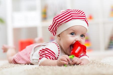 massage enfant: Bébé tenir un jouet couché sur le ventre dans la pépinière