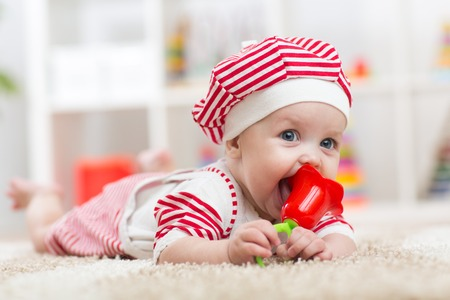 teether: Baby hold a toy lying on belly in the  nursery