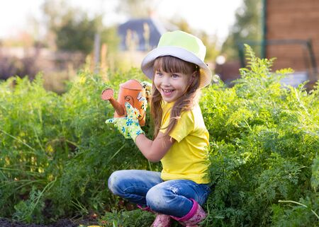 can: Little child girl posing with watering can