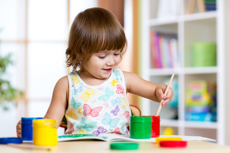 playschool: pretty kid girl painting with colours in kindergarten or playschool