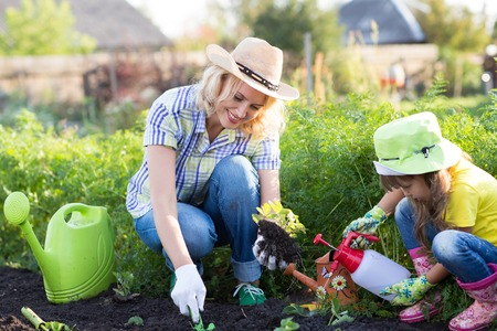 Mother and Daughter Child Watering Plants in Garden. photo
