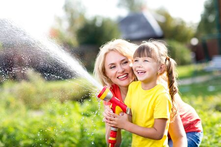 water plants: Portrait of little gardener girl with mother watering on lawn near house