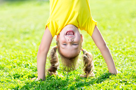 happy kid girl standing upside down on her head on grass in summerday