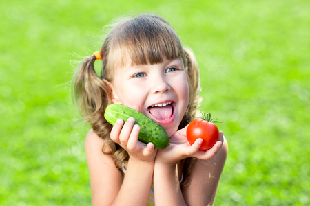 Adorable child little girl with vegetables outdoor photo
