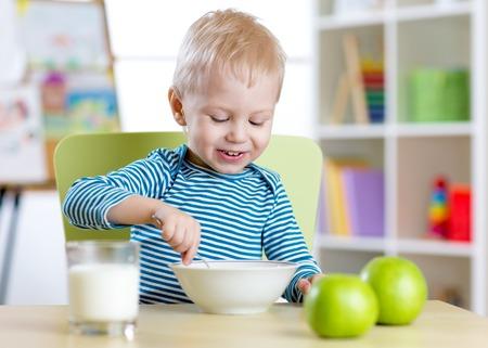 kid eats healthy food at home or kindergarten photo