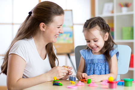 Child girl with her mother modelling from play clay