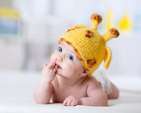 funny baby weared giraffe hat lying on bed in nursery