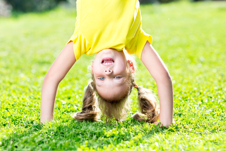 headstand: Happy child girl have a fun standing on her head among grass