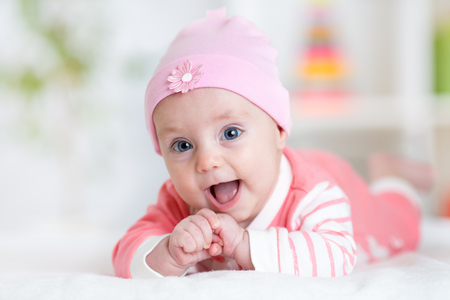 Cute baby girl. Smiling child lying on white bed in nursery room Archivio Fotografico