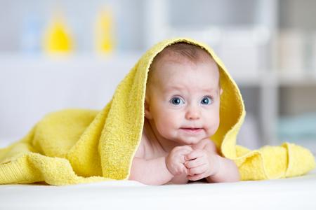 bebé divertido cubierto toalla suave. El niño lindo acostado en la cama después del baño o ducha en la sala de estar Foto de archivo