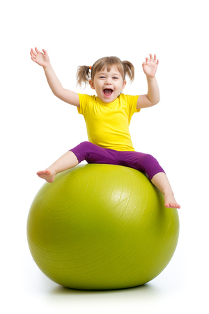fit ball: child girl doing gymnastics with fit ball over white background