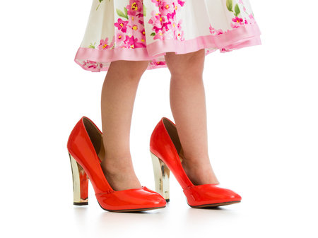 girl shoes: child girl trying mothers shoes on her feet isolated Stock Photo