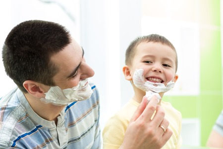shaving father with child son having a fun in bathroom