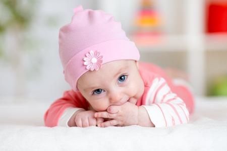 Baby teething sucks fingers. Infant kid lying in nursery room