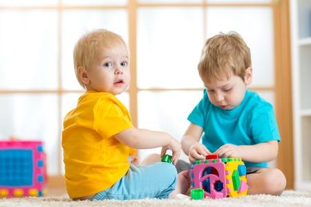 Kids boys playing in the nursery room