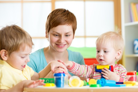 mother teaches children to work with colorful play clay toys