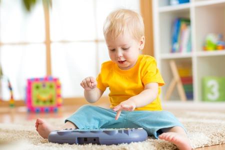 Garoto garoto feliz tocando piano brinquedo na sala de berçário