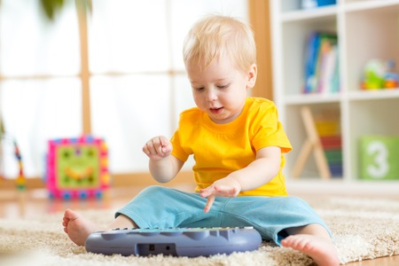 Happy kid boy playing piano toy in nursery room Stock Photo