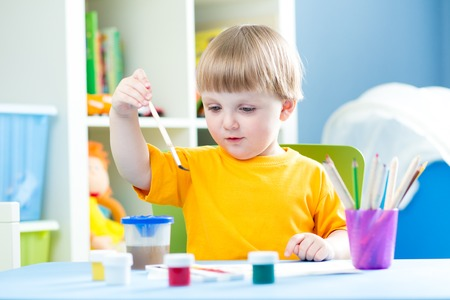 playschool: kid boy playing and painting at home or kindergarten or playschool