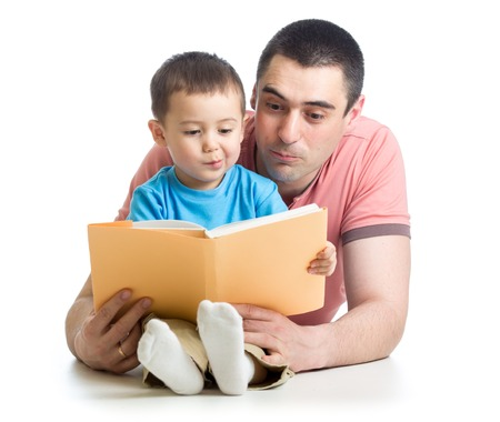 kid boy and his father read a book on floor at home Stock Photo