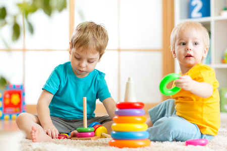 day care: Toddlers kids playing with wooden blocks on floor at home