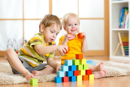day care center: Preschooler children playing with colorful toy blocks. Kid playing with educational wooden toys at kindergarten or day care center. Toddler boys in nursery room.