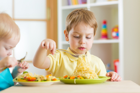 Preschool children eat healthy food in kindergarten or home Banque d'images