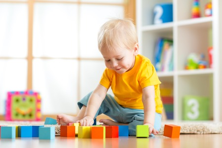 day care center: Preschooler child playing with colorful toy blocks. Kid playing with educational wooden toys at kindergarten or day care center. Toddler in nursery room. Stock Photo