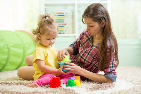 child care: babysitter with kid girl playing in nursery