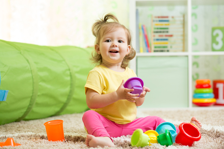 happy kid little girl playing with toys indoors