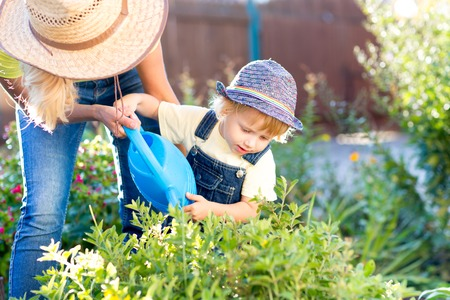 Child boy helps to his mother working in the garden in holiday