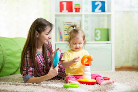 plaything: cute mother and kid girl playing together indoor at home