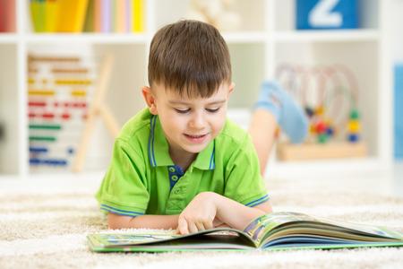 kid book: cute kid boy reading a book at home