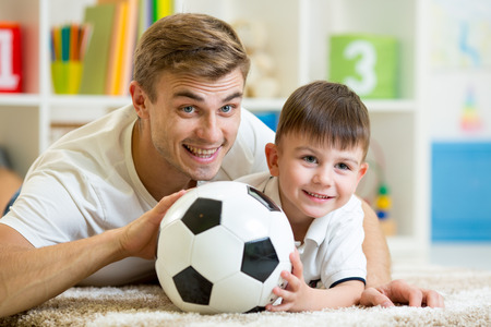 child boy and father playing with football