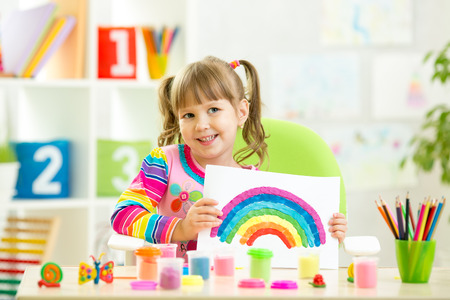 tinkering: child girl showing plasticine rainbow making by her hands Stock Photo