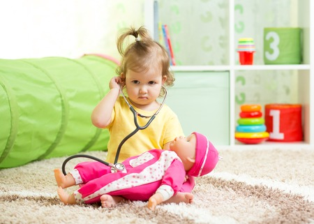 Kid Girl Playing Doctor With A Doll In Playroom Stock Photo