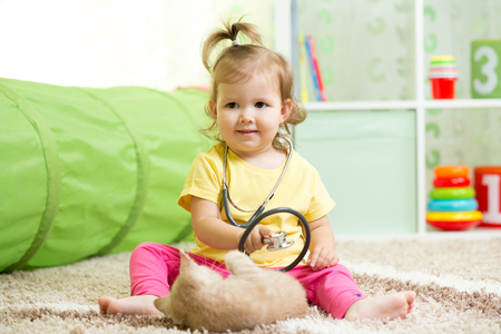 playschool: Child Girl Playing Doctor With A Cat In Nursery
