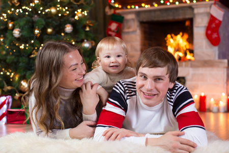 Happy parents and child have a fun near Christmas tree at home. Father, mother, son celebrating New Year together Stock Photo