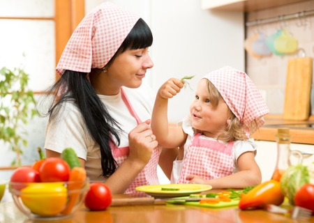 Happy mother and child daughter with salad n the kitchen Stock fotó
