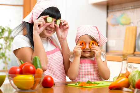 mother and kid daughter preparing healthy food and having fun photo
