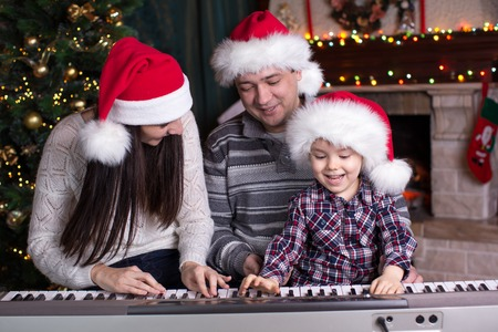 Family - mother, father and kid wearing santa hats playing the piano over festival christmas background