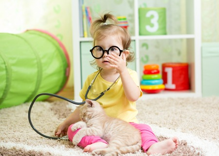 Child Girl Playing Doctor With A Cat Kitten In Nursery Stock Photo