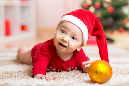 Funny baby wearing Santa hat and suit. Kid boy lying on tummy in front of Christmas tree at home photo
