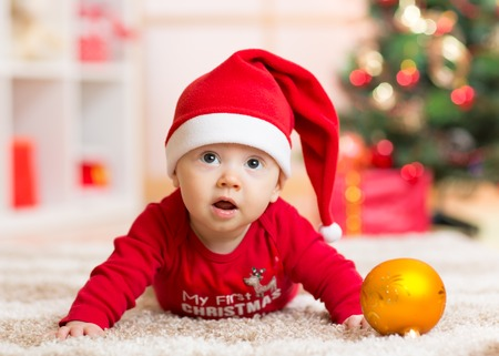 Funny baby lying on tummy wearing Santa hat and suit on floor in front of Christmas tree photo