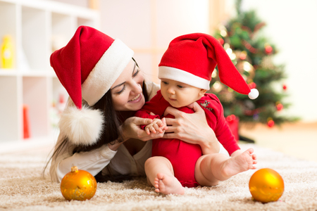 Mother and baby in santa red dress smile on a background of Christmas trees in the interior of the house photo