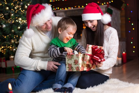 holidays, presents, christmas concept - happy family - mother, father and child boy open gift box photo