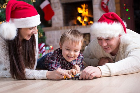 Little boy playing with toy cars with his parents under the christmas tree photo