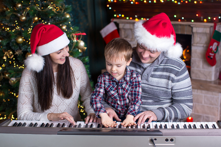 Family - mother, father and kid wearing santa hats playing the piano over festival christmas background photo