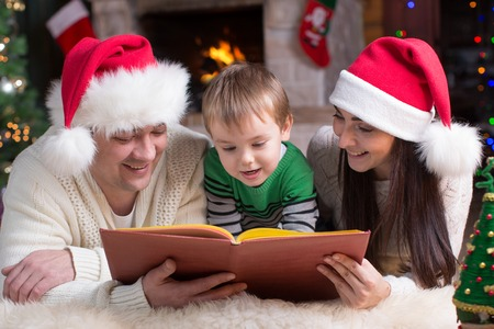 Happy family of three reading together on Christmas evening photo